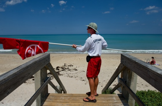 VERO BEACH - Nathan Rieck, lifeguard supervisor with the City of Vero Beach, takes down the double-red flag while closing down the Humiston Park lifeguard stand for the day on Wednesday afternoon. The flags, which signify the beach is closed to swimming, were flying due to a shark attack.