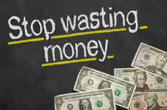 stop-wasting-money-text-blackboard-49612146